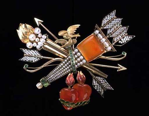 This elegant brooch takes as its theme the symbols of love. Cupid's bow and arrows (two loose and three in the quiver) are arranged with a pair of doves, two hearts on fire and a hymeneal torch (named after Hymen, the Greek goddess of marriage). They form a diagonal composition of great effectiveness. Like most jewellery produced in France soon after the Revolution of 1789, it is made of thin gold and contains few precious stones.