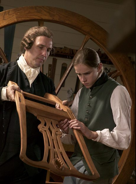 Apprentice and master at the Hay Cabinetmaker's shop inspect the workmanship on a chair. Historic Colonial Williamsburg, Williamsburg, Virginia