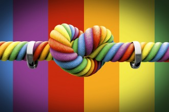 A coarse rope in the colors of the homosexual flag with a knot tied in the middle and two silver rings hanging on it on an isolated background